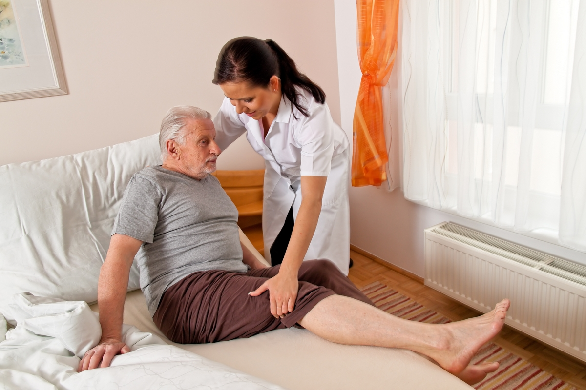 a caregiver assisting an elderly man