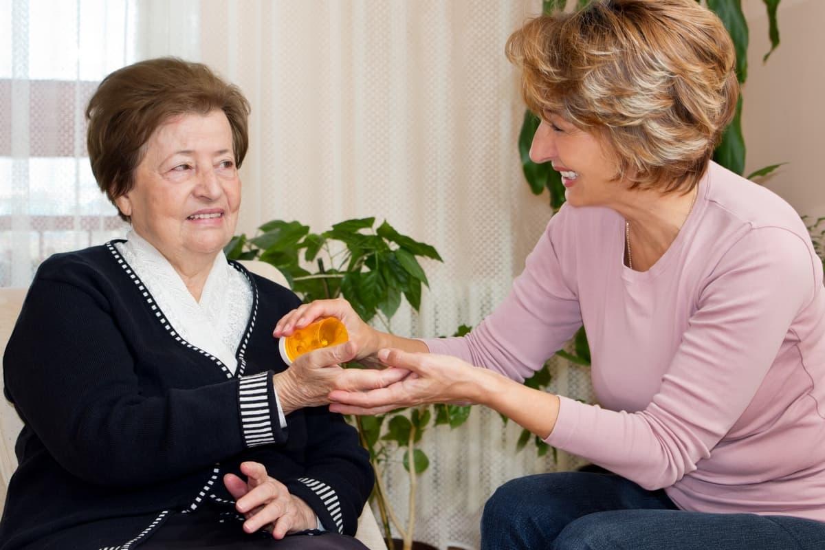 a woman giving an elderly woman medicine